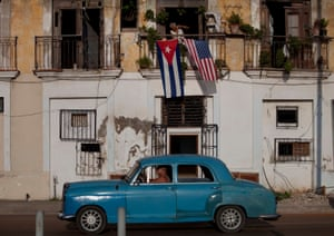 A car drives past as American and Cuban flags fly on the balcony of a home in Havana