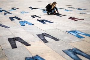 A demonstrator places a pair of jeans on the ground during a flash mob protest in Turin, Italy for Denim Day.