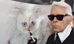 Karl Lagerfeld poses next to a painting of Choupette