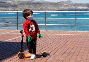 A child plays with his scooter on the promenade of Las Canteras Beach on the island of Gran Canaria