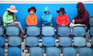 Rain causes spectators to don jackets and hats