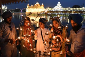 Sikh devotees light candles on the occasion of the 417th anniversary of the installation of the Guru Granth Sahib, at the illuminated Golden Temple in Amritsar