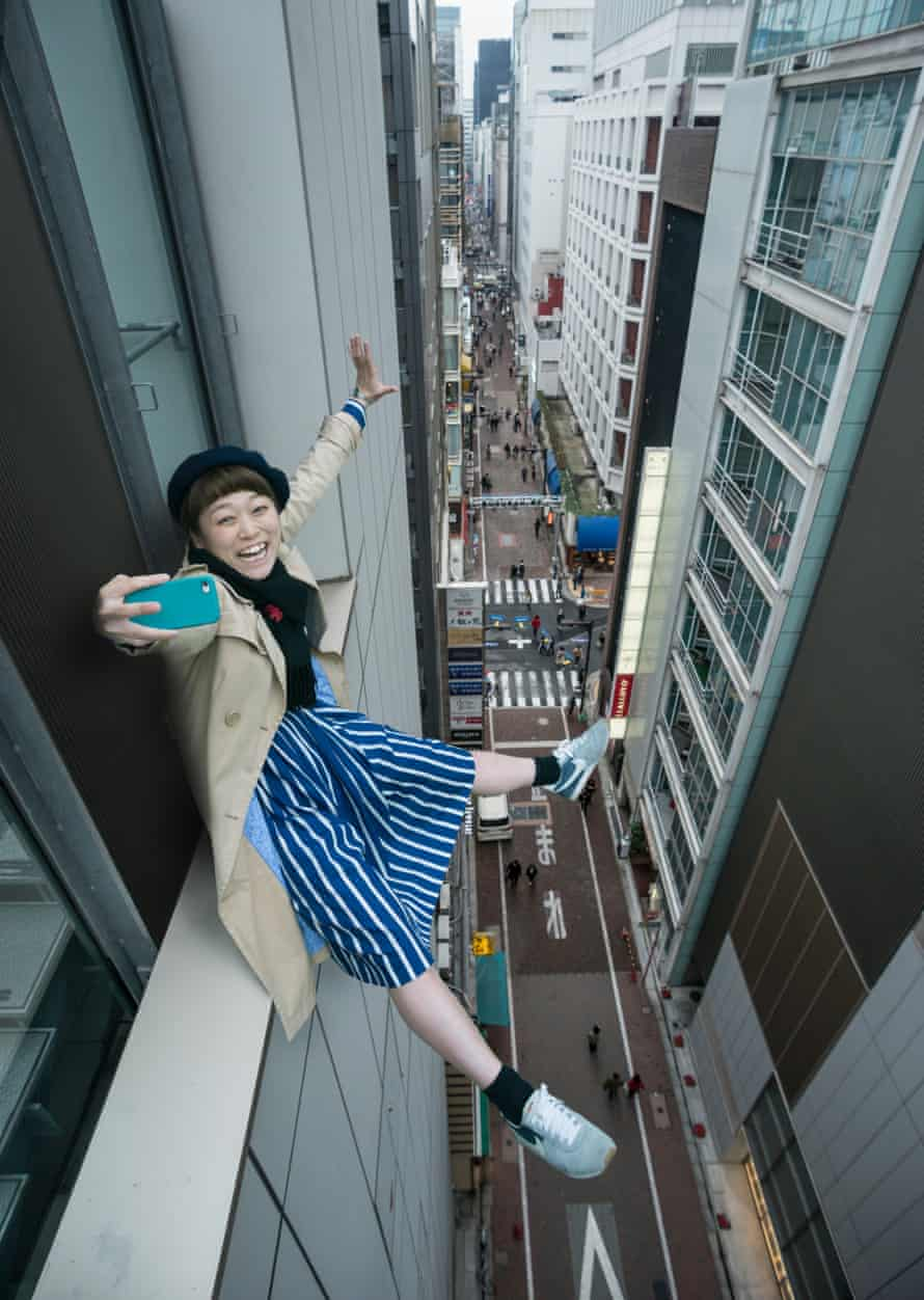 A woman perches on a window ledge in Tokyo to take a selfie.