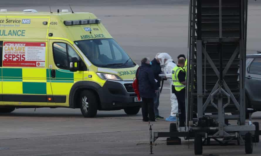NHS West Midlands ambulance service staff with passengers from the Grand Princess cruise ship at Birmingham airport, March 2020