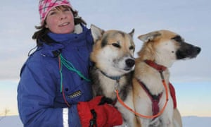 Dog sledding, Norway. Woman holding two husky dogs while in the snow in Norway.