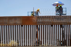 A group of workers reinforces security with barbed wire along a US border wall in Ciudad Juarez, Mexico.