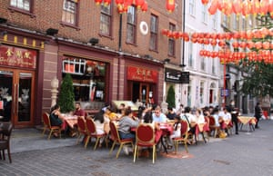 People eat at outside tables at a restaurant with all the colourful lanterns in Chinatown, London. A far cry from the empty, desolate streets of 'lockdown' days, Chinatown has embraced the new outdoor dining culture and the streets are busier and restaurants doing good business again in Gerrard Street, London, UK on 1 August 2020.