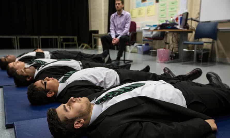 Teacher Dominic Morris and pupils practicising relaxation and meditation techniques.
