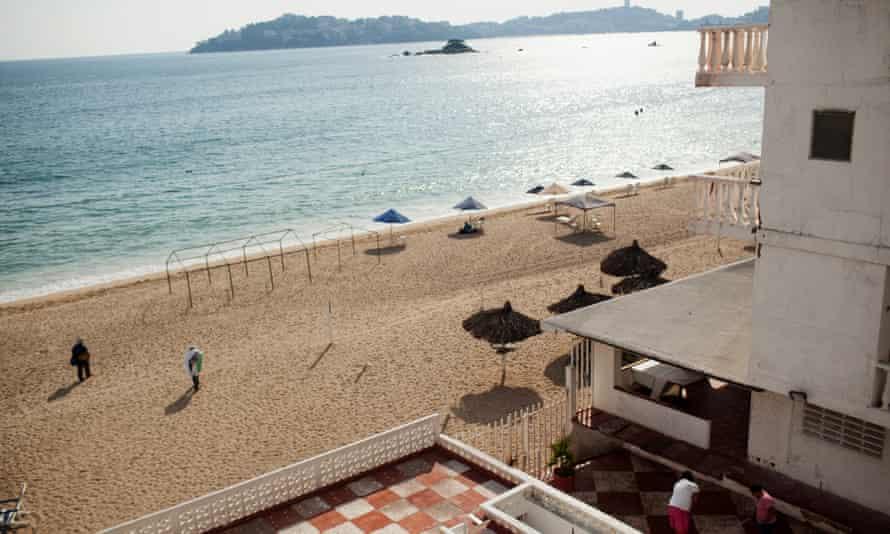 People walk on beach in Acapulco