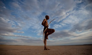 A bushman from the Khomani San community strikes a traditional pose in the Southern Kalahari desert, South Africa. The San still hunt animals as our common ancestors did.