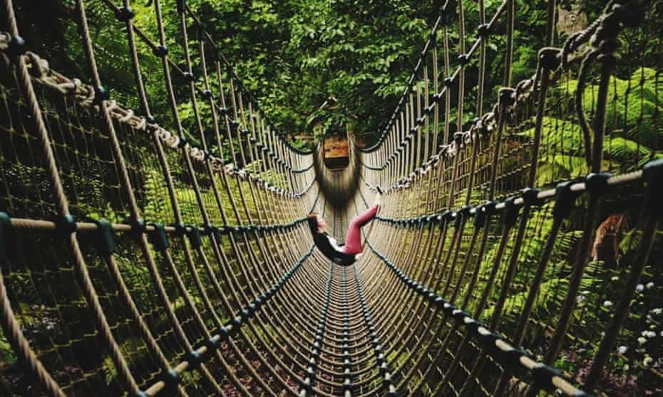 Side View Of Woman Sitting On Rope Bridge at The Lost Gardens of Heligan.