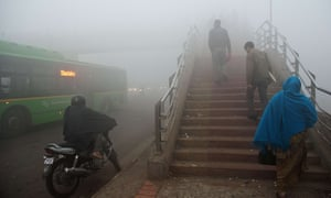 Commuters struggle through the smog in Delhi. India's air pollution costs an estimated one million lives a year.