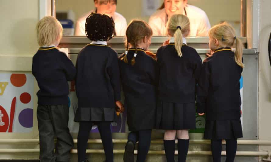 Schoolchildren line up for lunch