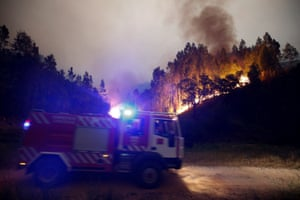 Firefighters work to put out a forest fire near Bouca in central Portugal