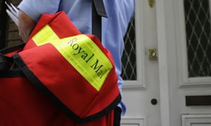 A postal worker delivers mail to a home in London.
