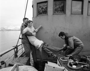 """Arctic Islands of Lofoten, Norway, 1959 Norwegian Navy frogmen removing Baldwin from his dry suit after one of his dives to photograph the migrating cod fish. """"Their help was indispensible as I had never received schooling on how to use Scuba equipment."""""""