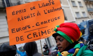 A woman holds a placard as she attends a protest against slavery outside the Libyan embassy in Paris.