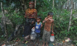 Rohingya refugees stand by the road in the rain outside their camp near Cox's Bazar, Bangladesh