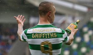 Celtic's Leigh Griffiths holds a glass bottle that appeared to have been thrown at him from the stands at Windsor Park.