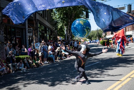 A performer acts as the moon to the Earth during the 30th annual Fremont Solstice Parade.