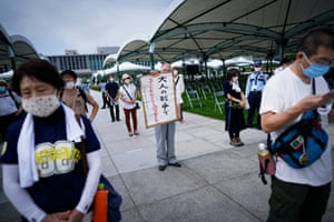 An elderly man holds up a sign that reads 'Don't let children cry because of adults' war' as he queues in line to pray at Peace Memorial Park