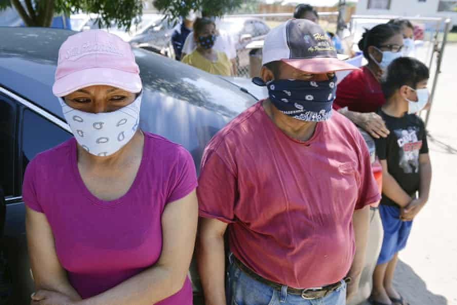 Farm workers and their families wait in line for donations of food and masks on 9 May in Fresno county.