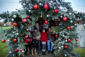 Wernfried and Adelheid Meyer sit with their son Dirk at a festive bus stop in Viehle, Germany
