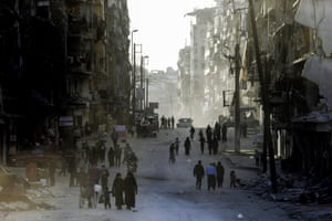 A picture taken on March 9, 2017 in the northern Syrian city of Aleppo, which was recaptured by government forces in December 2016, shows people walking in the formerly rebel-held al-Shaar neighbourhood