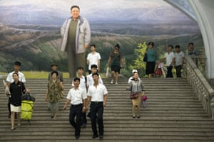 People pass a large picture of Kim Jong-il as they walk through a station on the Pyongyang metro.