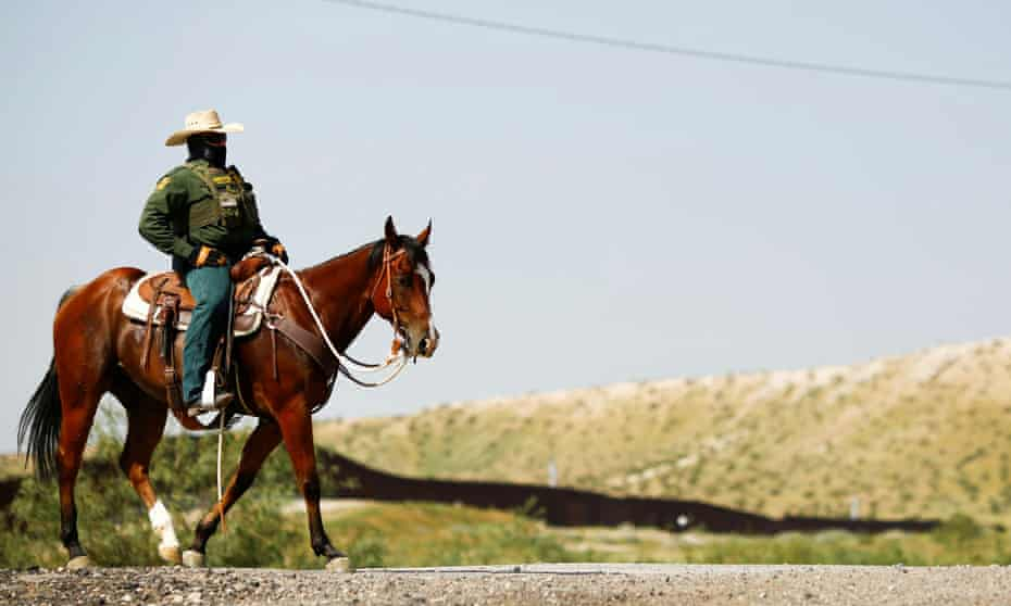 US border patrol agents on horseback are searching for migrants trying to enter the United States along the US-Mexico border.