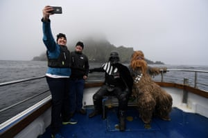 Holidaymakers take a selfie, along with Star Wars fans dressed in costume as Darth Vader and Chewbacca, on a boat trip to Skellig Island during the inaugural 'May The 4th Be With You' festival.