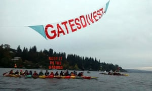 Kayactivists paddle on Lake Washington with banners in front of the Gates Medina mansion in Seattle.