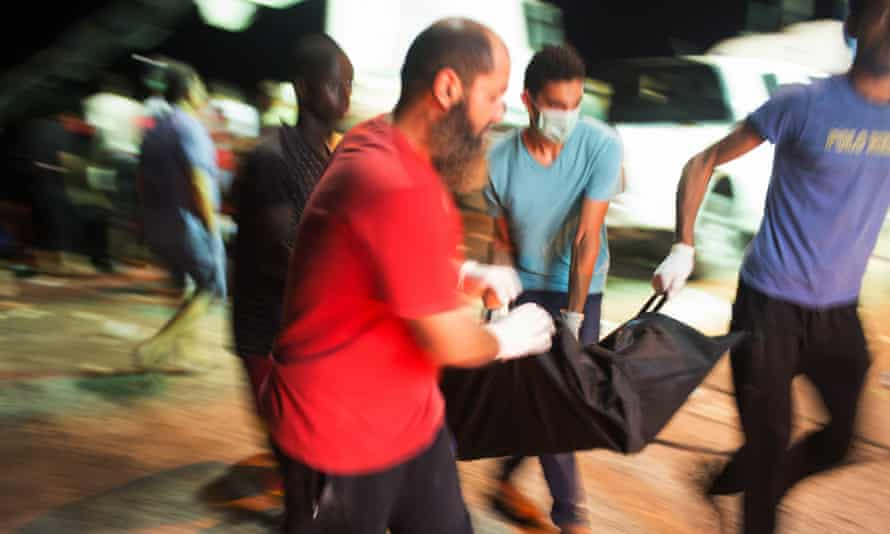Rescuers remove a body after a boat sank off the coast of Zuwara, Libya