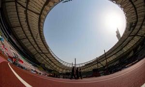 Officials walk on the track inside the Khalifa International Stadium in Doha