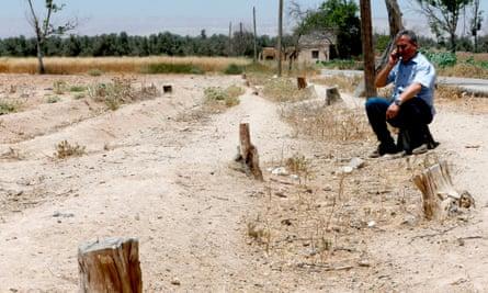 A man sits on a barren piece of farmland in Eastern Ghouta, Syria.