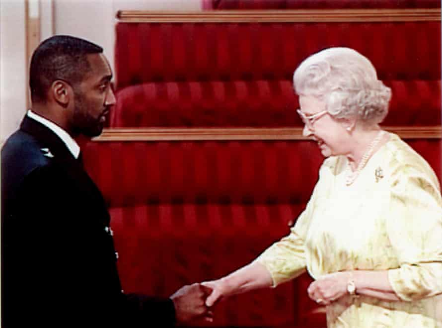 Leroy Logan shakes hands with the Queen after being awarded an MBE in 2000