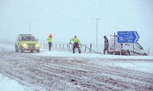 Traffic officers prepare to pull a van out of a ditch off the A6 near the village of Shap in Cumbria, UK.