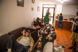 German Blanco's daughter July checks on him as he lies on a couch connected to an oxygen tank at his home in Callao.