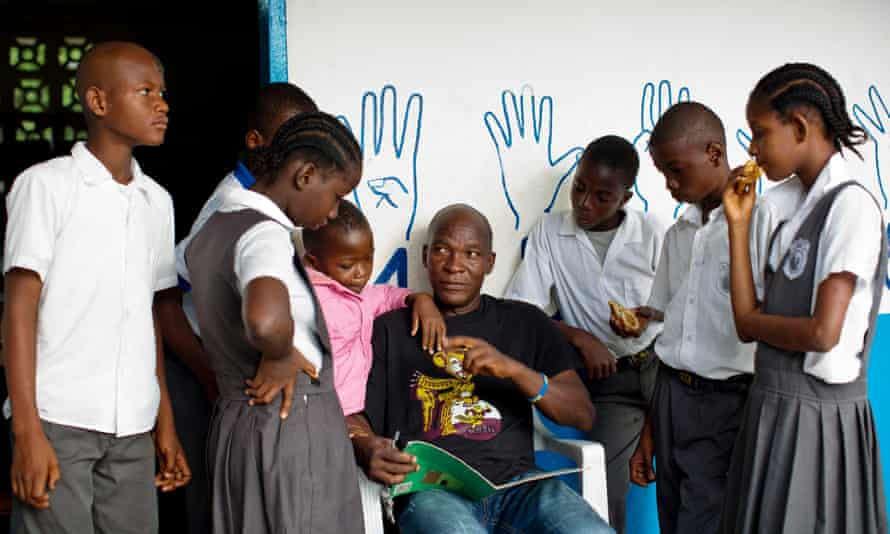 A teacher with a group of children at the Oscar Romero school for the deaf in Tubmanburg.