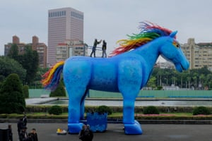 Taipei, Taiwan. Two people stand on a statue of a horse during a photo call for an art performance by Paper Windmills Theatre