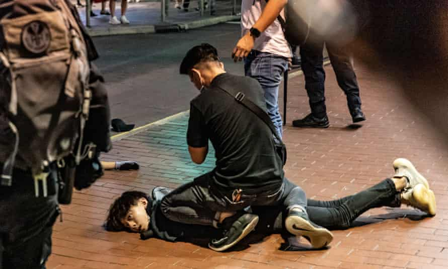 An anti-government protester is detained by police in Mongkok.