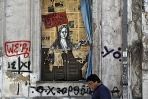 A man walks past a political graffiti in central Athens by artist Bleeps