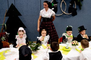 Children in traditional costumes eat and drink during the Bird Wedding celebrations
