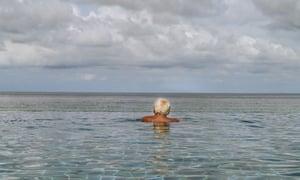 Elderly man swimming in infinity pool