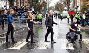 Prince Harry and Jon Bon Jovi cross the road outside Abbey Road Studios in rainy London.