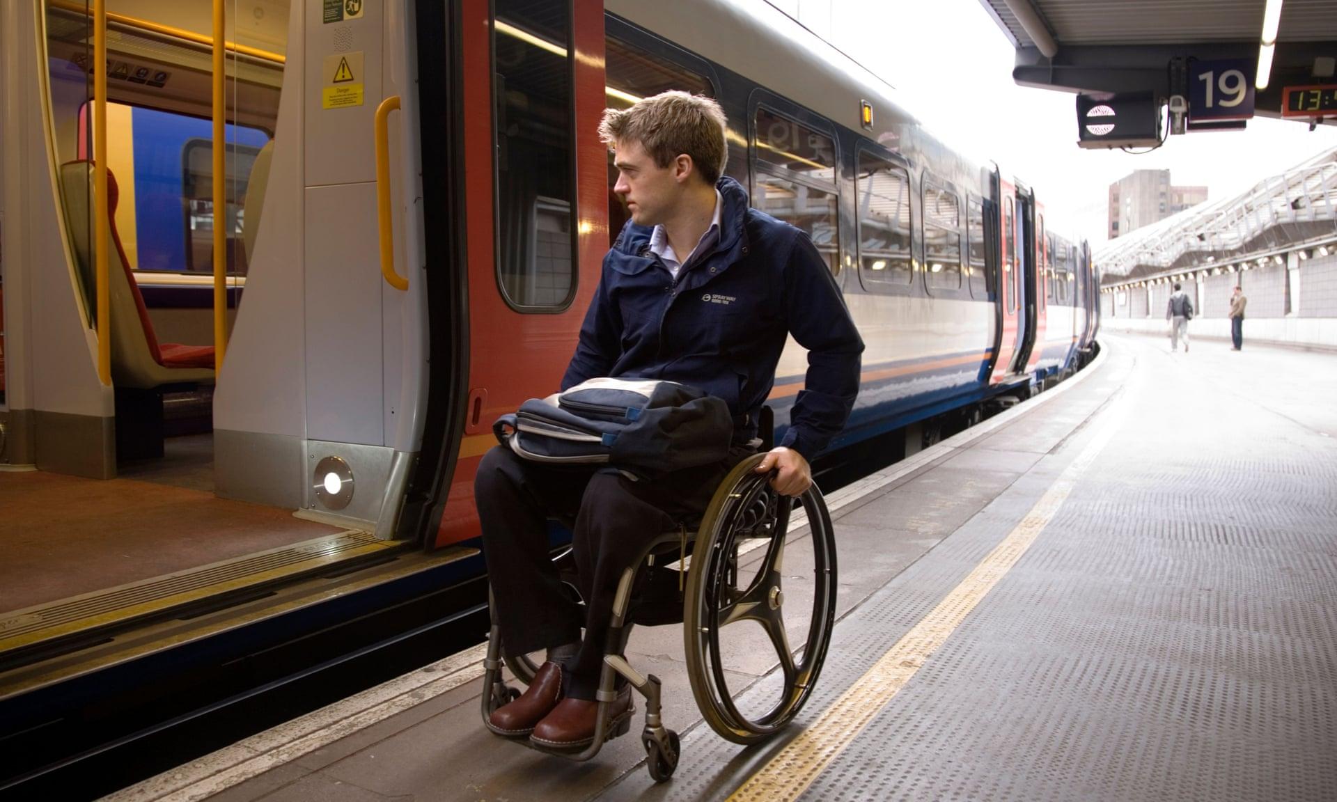 Un usuario de silla de ruedas se prepara para intentar abordar un tren en una estación de Londres. Fotografía: Alamy