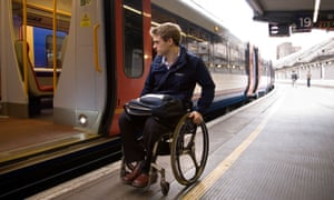 A wheelchair user prepares to attempt to board a train at a London station.