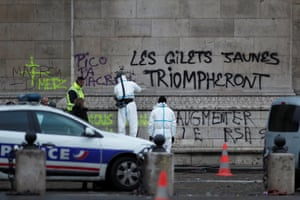 Police at work near graffiti reading 'the yellow vests will triumph' sprayed on the Arc de Triomphe