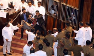 A pro-Rajapaksa member of parliament confronts police escorting the house's speaker.