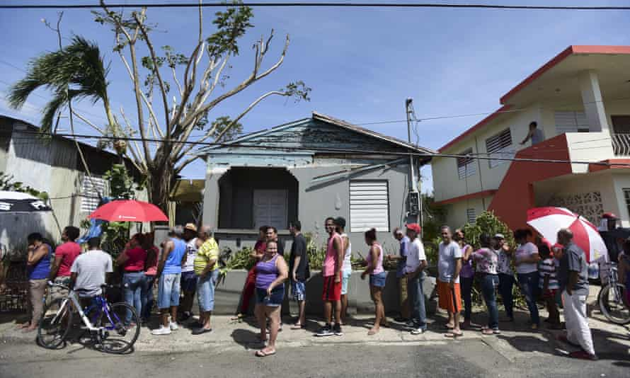 People wait in line to receive supplies from the national guard, in San Juan, Puerto Rico.